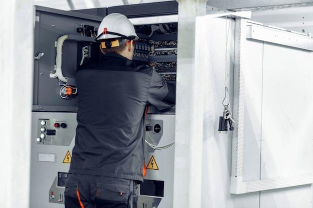 Ingegnere che lavora su apparecchiature di controllo e manutenzione per il cablaggio sull'armadio plc