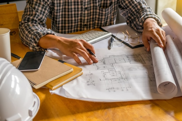 Ingegnere che lavora su blueprint.construction concept. strumenti di ingegneria. effetto retro del filtro retroilluminato, fuoco morbido (messa a fuoco selettiva)