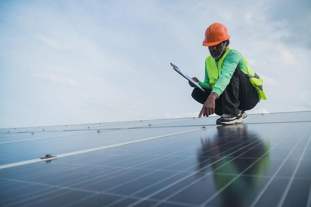 Ingegnere che lavora sul pannello di manutenzione nella centrale elettrica solare