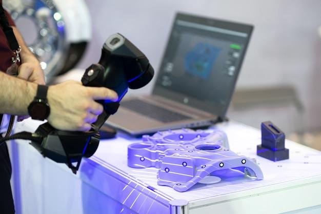 Ingegnere che lavora sull'ambito dello scanner per eseguire la scansione della forma del pezzo sul computer