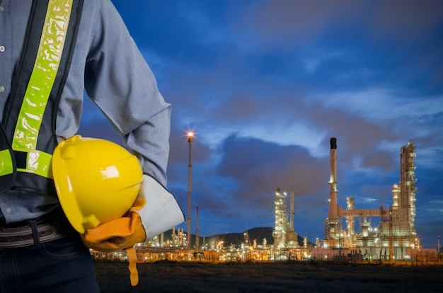 Ingegnere che tiene casco giallo con raffineria di petrolio.