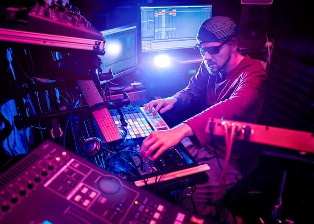 Ingegnere del suono che lavora al pannello di missaggio nello studio di registrazione del suono.