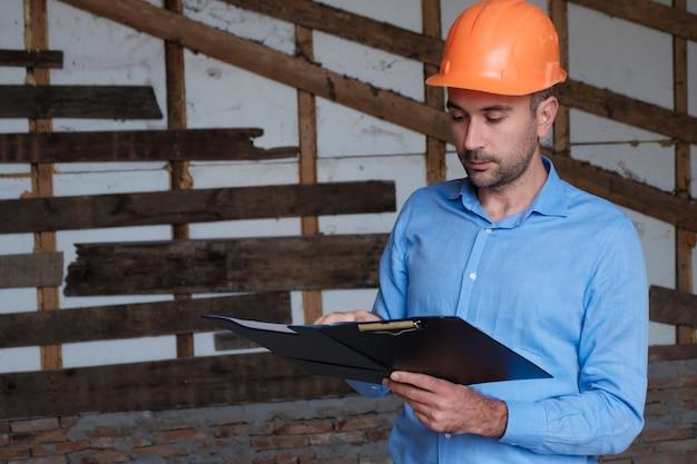 Ingegnere dell'architetto del costruttore di costruzioni che indossa casco arancio