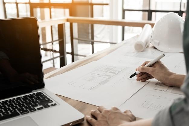 Ingegnere dell'architetto inizia a disegnare un progetto di casa sulla scrivania in ufficio presso il cantiere di costruzione e gli strumenti di ingegneria