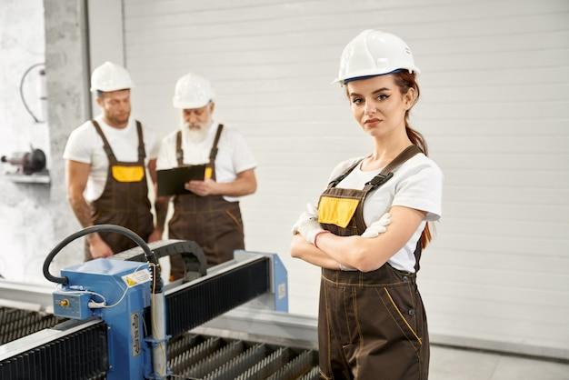 Ingegnere della donna che posa con i lavoratori sulla fabbrica di lavorazione dei metalli.