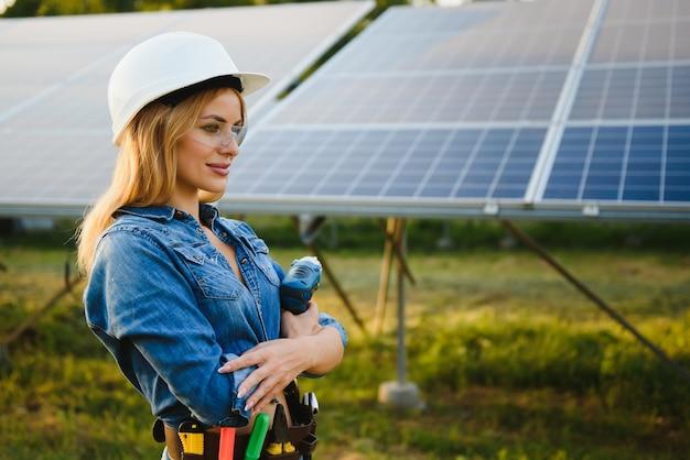 Ingegnere delle donne che lavora al controllo delle apparecchiature presso la centrale solare a energia verde