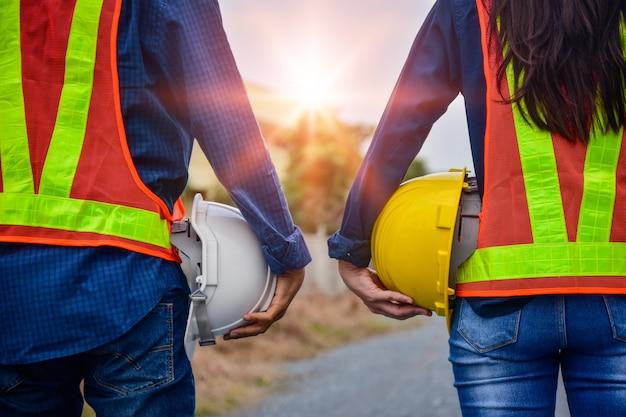 Ingegnere delle donne e dell'uomo che tiene la sicurezza dell'elmetto protettivo stare all'aperto progetto di gestione di lavoro di squadra