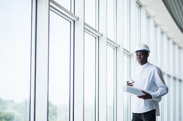 Ingegnere di costruzione afroamericano davanti ai modelli della tenuta della costruzione contro le finestre