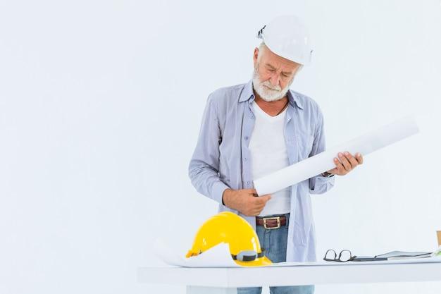 Ingegnere di costruzione serio senior con il modello della tenuta della mano del casco in studio con spazio bianco per testo