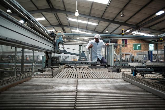 Ingegnere di fabbrica che controlla una linea di produzione