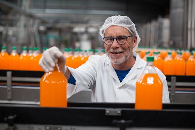 Ingegnere di fabbrica che esamina una bottiglia di succo