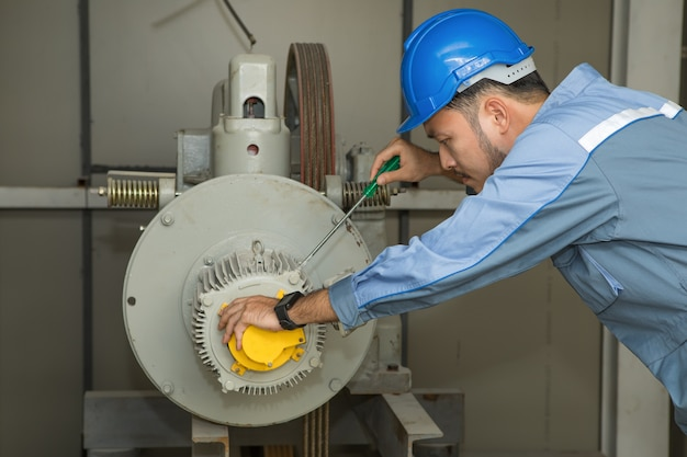 Ingegnere di manutenzione che ripara ascensore motore per ascensori