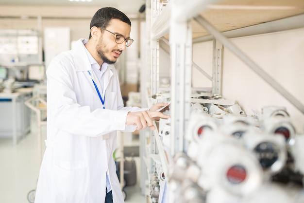 Ingegnere di prova concentrato che esamina i sensori di pressione