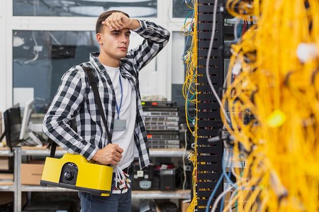 Ingegnere di rete stanco con una scatola che lavora agli switch ethernet