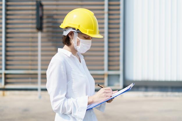 Ingegnere donna verifica rapporto di costruzione, scrivendo un rapporto tecnico sul processo di fabbricazione.
