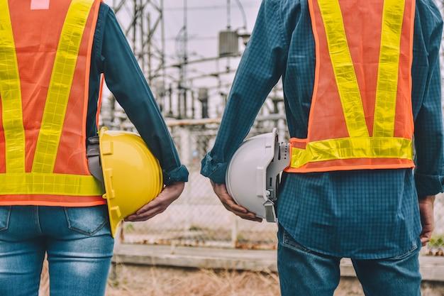 Ingegnere due persone in possesso di elmetto indossare tuta di sicurezza