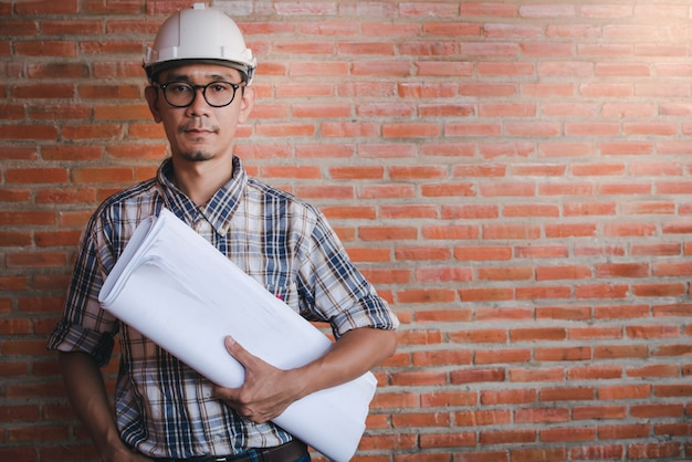 Ingegnere edile asiatico o architetto in piedi in possesso di un documento nello stile di un progetto architettonico in un cantiere di sfondo arancione