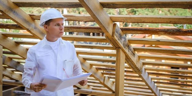 Ingegnere edile o architetto con le cianografie sul cantiere