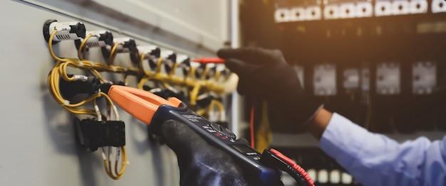 Ingegnere elettrico che utilizza un multimetro digitale per controllare la tensione di corrente sul quadro di distribuzione principale.