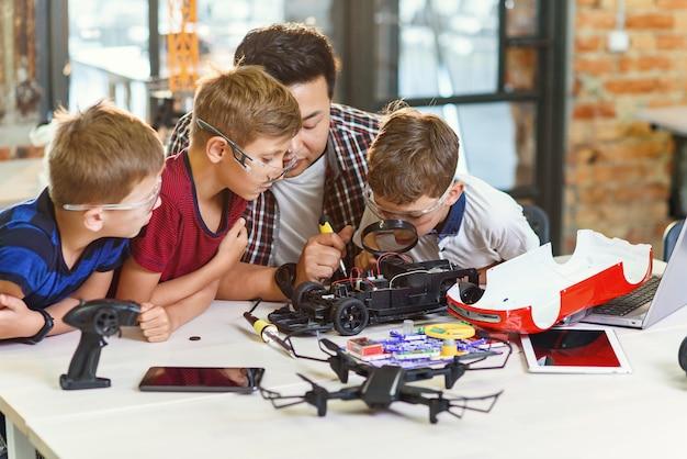 Ingegnere elettronico con scolari europei che lavorano nel laboratorio scolastico moderno e testano un modello di auto elettrica