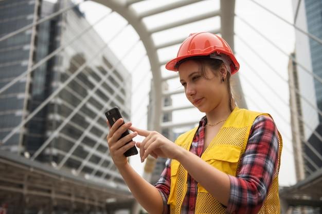 Ingegnere femminile americano che utilizza smartphone al sito