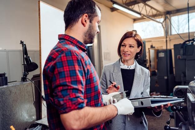 Ingegnere femminile che consulta l'operatore della macchina del tornio facendo uso del calibro