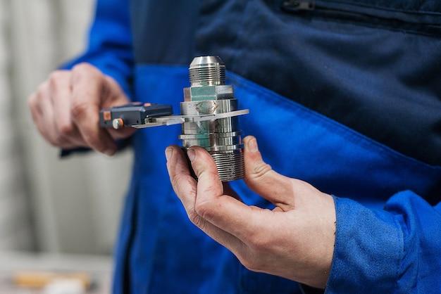 Ingegnere in fabbrica con apprendista controlla la qualità dei componenti
