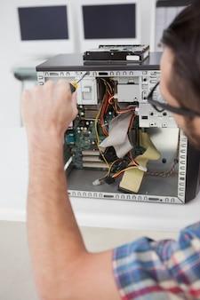 Ingegnere informatico che lavora alla console rotta con il cacciavite