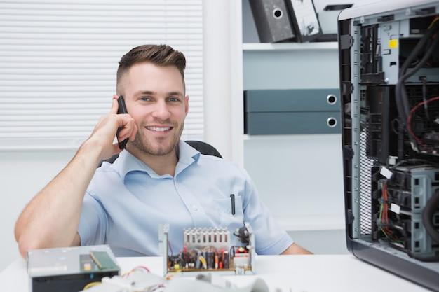 Ingegnere informatico sorridente su chiamata dal cpu aperto