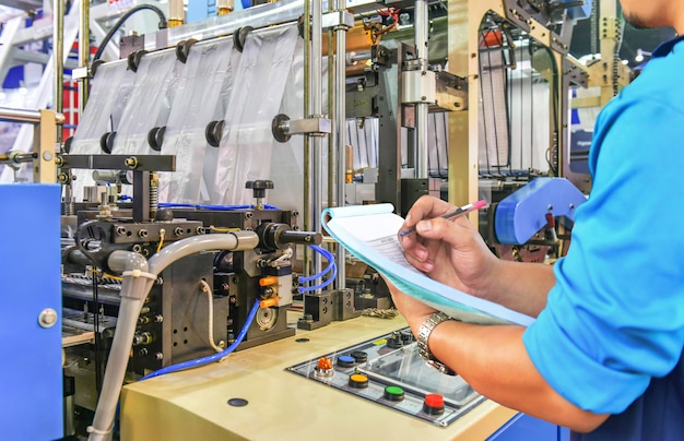 Ingegnere manager che controlla la linea di produzione automatizzata