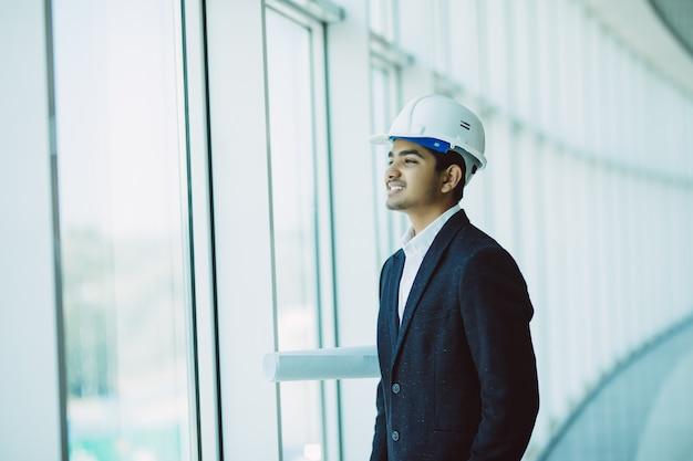 Ingegnere maschio indiano dell'appaltatore del sito con il casco che tiene la carta della stampa blu che cammina al cantiere