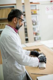 Ingegnere maturo in laboratorio esamina piastrelle di ceramica