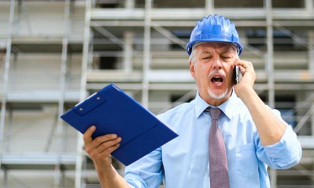 Ingegnere senior arrabbiato che grida al telefono