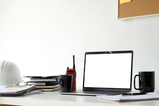 Ingegnere strutturale e architetto desktop con schermo vuoto laptop e casco di sicurezza