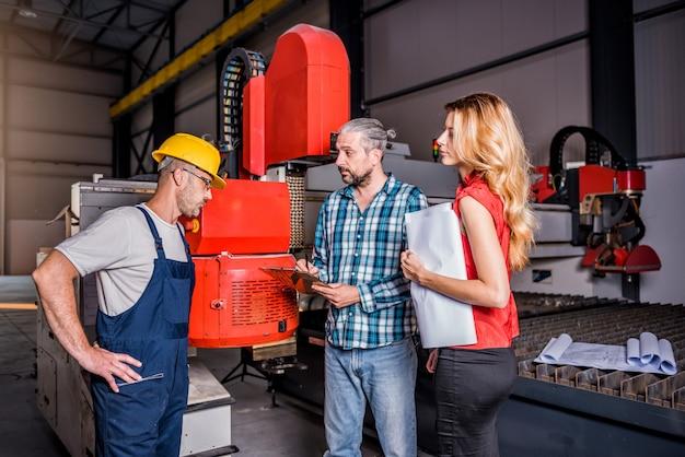 Ingegneri che controllano l'installazione della nuova macchina per plasma cnc