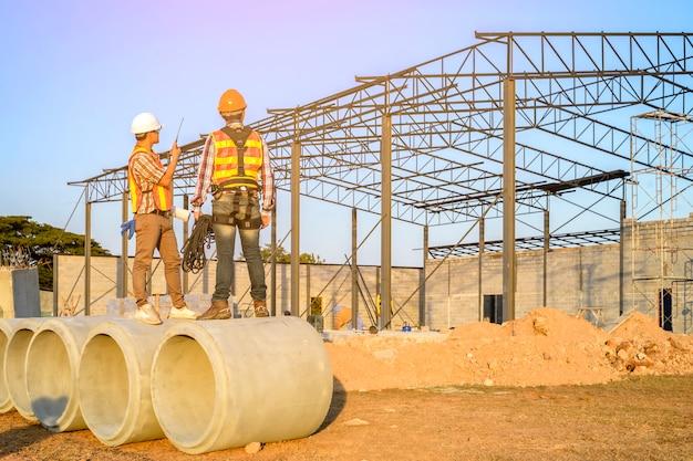 Ingegneri che guardano la squadra di muratori sull'alta piattaforma d'acciaio