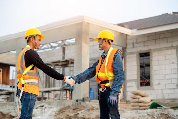 Ingegneri che stringono le mani al cantiere, concetto di edificio residenziale in costruzione.