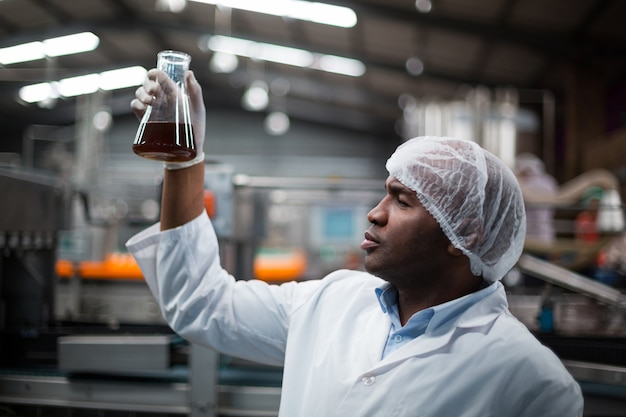 Ingegneri di fabbrica che controllano un campione di bevanda