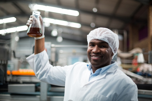 Ingegneri di fabbrica che tengono un campione di bevanda