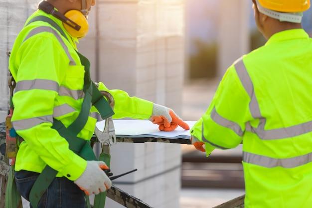Ingegneri e lavoratori asiatici consultati insieme per la pianificazione e lo sviluppo della costruzione, concetto di lavoro di squadra di costruzione.