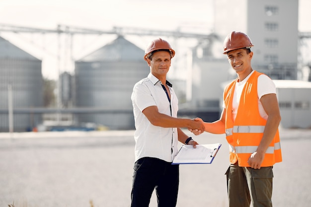 Ingegneri in caschi che fanno una pausa la fabbrica
