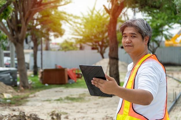 Ingegneria in piedi di fronte al cantiere e utilizzo di tablet per la costruzione.