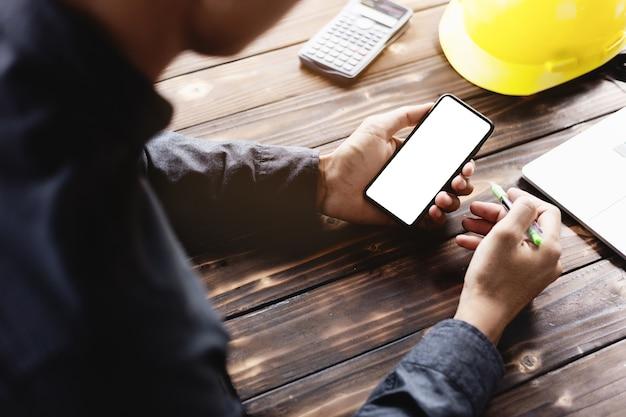 Ingegneria utilizzando telefono cellulare sulla scrivania