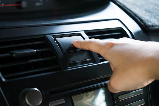 Inger toccare il pulsante di emergenza sul cruscotto dell'auto.