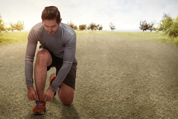 Inginocchiamento asiatico bello dell'uomo che lega le scarpe da corsa che si preparano per pareggiare