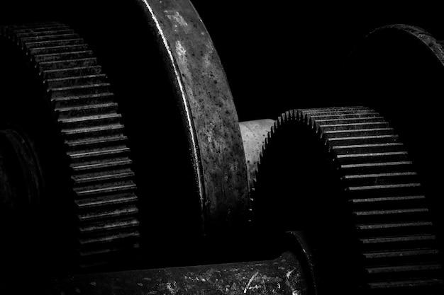 Ingranaggio di metallo arrugginito sullo sfondo scuro - monocromatico