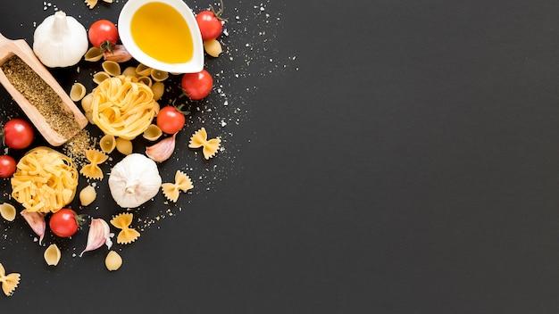 Ingrediente crudo con tagliatelle; conchiclioni; tagliatelle; farfalle; olio su sfondo nero