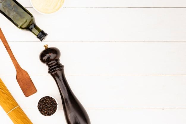 Ingrediente della pasta e utensile della cucina su fondo bianco