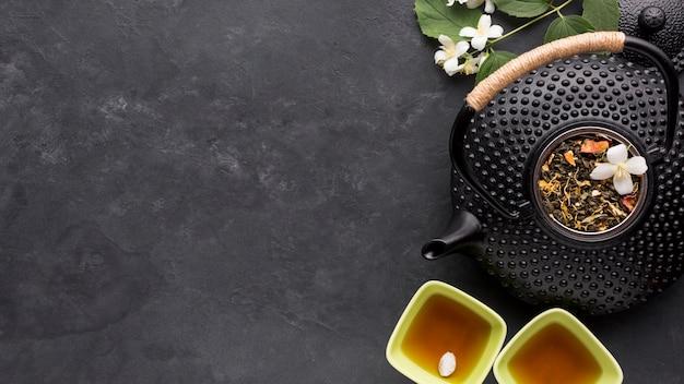 Ingrediente secco dell'erba del tè con la teiera nera sul fondo della pietra dell'ardesia