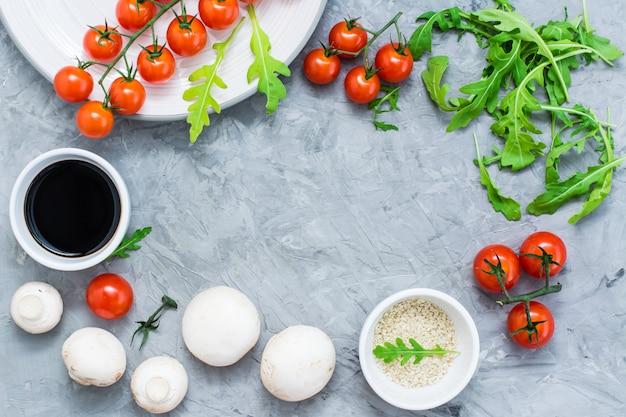 Ingredienti alimentari cornice foderata su uno sfondo concreto: pomodorini, funghi, rucola, sesamo e salsa balsamica. vista dall'alto